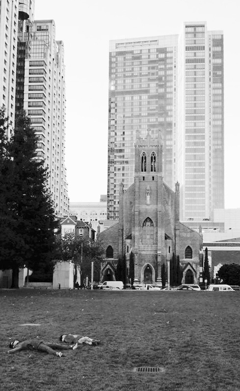 Kids laying on a grass, a house of worship, and a tall modern building